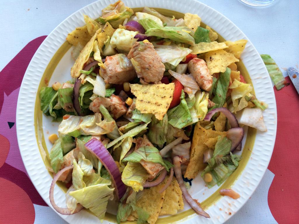 Retten består av blandet salat, kylling og tacoskjell, krydder og salsa.